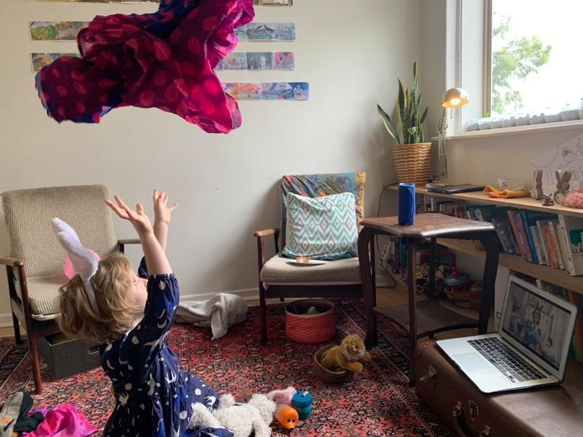 Little girl throwing scarf in the air watching music class on screen
