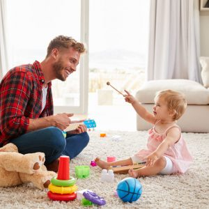 The-Rhythm-Tree-father-and-young-daughter-playing-toy-instruments--WDKHPXV